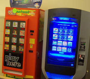 A current Iowa Lottery vending machine on the left, and a new type touch screen machine on the right.