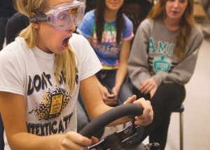 Teens use a driving simulator.