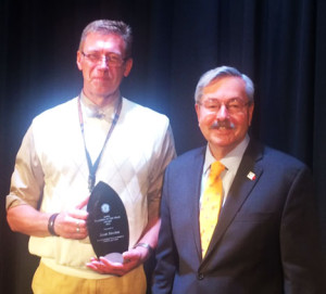 Scott Slechta holds the award presented by Governor Terry Branstad.