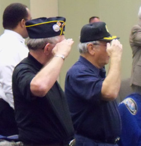 Veterans salute as the American flag is posted.
