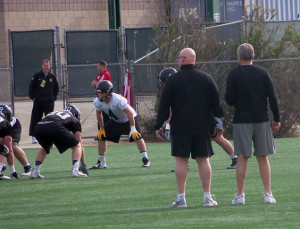 Coach Kirk Ferentz (right) watches practice.