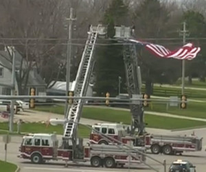 Des Moines fire trucks hoist a large flag that the funeral procession for Susan Farrell went under.