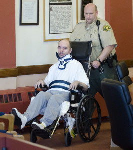 Jonathan Neunaber is wheeled into the courtroom.