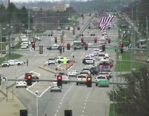 The funeral procession moved under a large American flag on the way to the cemetery.