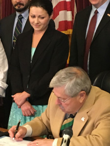 Ruth Lapointe watches Governor Branstad sign the bill.