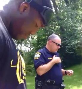 Faith Ekakitie waits as an officer checks his ID.