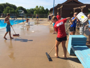 Workers scrub down the deck area of the Municipal Pool in Marion. Photo courtesy KCRG-TV.