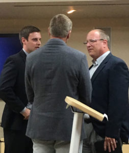 Jere Null, CEO of Prestage Foods of Iowa, (right), visits with plant supporters after a public hearing in Des Moines.