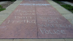 Messages of support for Police Chief Trelka written in chalk on the sidewalk outside Waterloo City Hall.