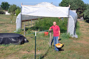 Farmer Rick Hornsby beside his seasonal high tunnel in Dallas County. (USDA photo)
