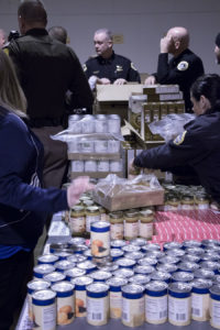 Preparing canned goods for food boxes.
