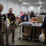 Law officers put together holiday food packages for the needy